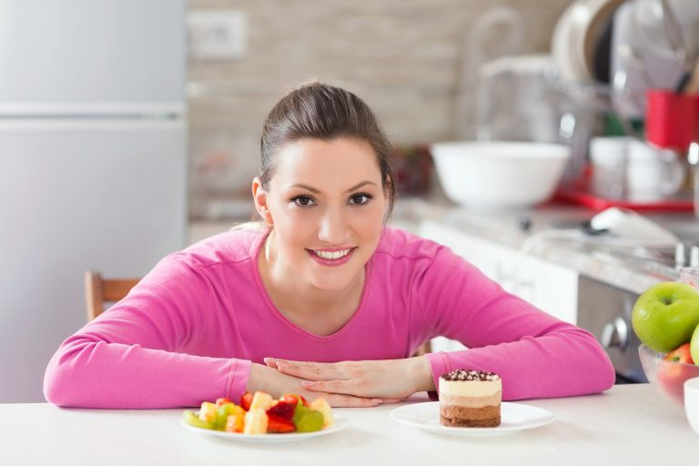 Beautiful smiling young woman is sitting at the table in the kitchen and trying to choose what to eat – healthy and fresh fruit salad or delicious chocolate cake.